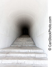 marble staircase leading to dark tunnel