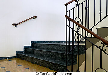 Marble steps with a handrail in the hallway