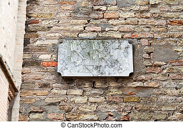marble street sign on old brick wall