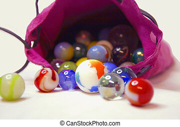 Some colorful marbles spilling from a magenta colored bag. This is a macro shot taken with a 70-300mm lens.