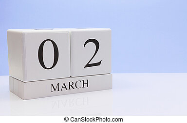 March 02st. Day 02 of month, daily calendar on white table with reflection, with light blue background. Spring time, empty space for text