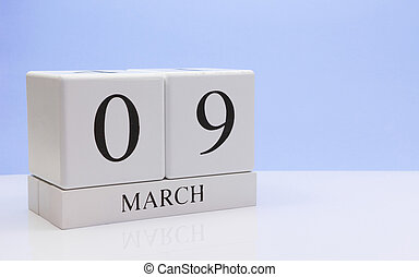 March 09st. Day 09 of month, daily calendar on white table with reflection, with light blue background. Spring time, empty space for text