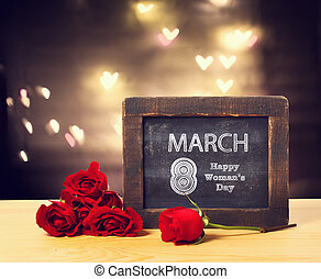 March 8 Womans day message on a small chalkboard with red roses
