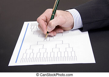 March Madness Businessman Hand Filling In Brackets - A...