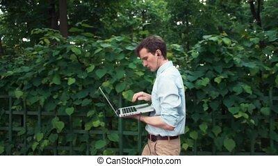 marche, asseoir, ordinateur portable, écouteurs, parc, jeune, banc, bas, utilisation, homme