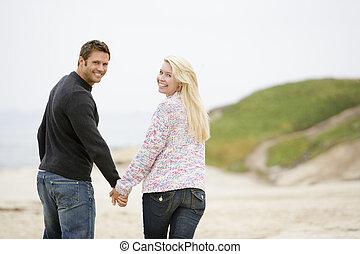 marche couples, à, plage, tenant mains, sourire