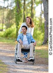 marche femme, homme, fauteuil roulant, pousser, couple, jeune, dehors