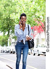 marche, femme, téléphone portable, rue américaine, africaine, heureux