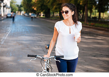 marche, femme, vélo, café, plat à emporter, lunettes soleil, sourire