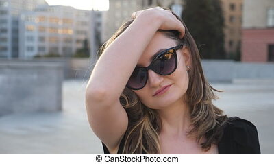 marche, redresse, hair., portrait, fin, girl, commuer, ville, lent, work., jeune regarder, confiant, appareil photo, séduisant, femme, lunettes soleil, business, rue., femme affaires, haut, figure, mouvement
