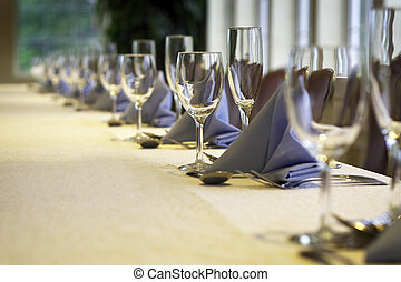 a line of wine glasses fading off in the distance, shallow depth of field. yellow linen
