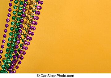 Mardi Gras beads against golden yellow background