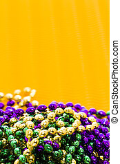 Mardi Gras beads yellow backgound.