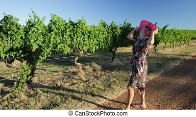 Margaret River Woman enjoys - Scenic landscape of vineyard...