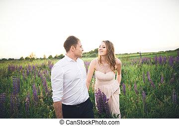 mariée marié, rissing, à, coucher soleil, sur, a, beau, champ, à, fleurs, romantique, couple marié