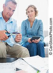marido, corte, tarjeta de crédito, en, mitad, con, esposa, con, cuentas, sobre la mesa, en casa, en, el, sala