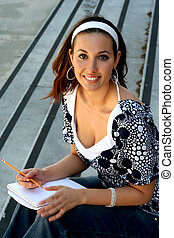 Female student sitting on stairs with a notebook and pencil