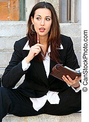 attractive businesswoman looking at camera holding planner and pen