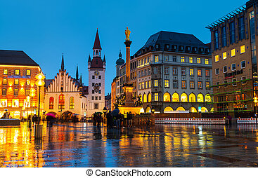 Marienplatz at night in Munich, Germany with old town hall and other buildings - cafes, bars, shops and restaurants. Motion blurred people.