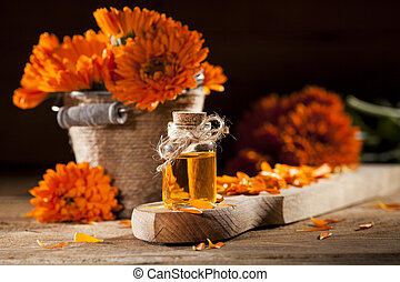 Essential oil made from marigold on rustic wooden background