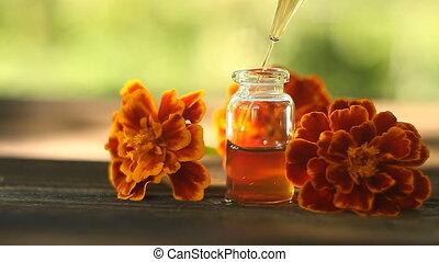 marigold essential oil in  beautiful bottle on table