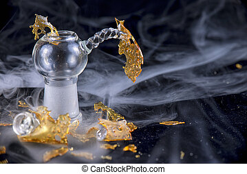 Marijuana oil concentrate aka shatter isolated with glass rig on black background