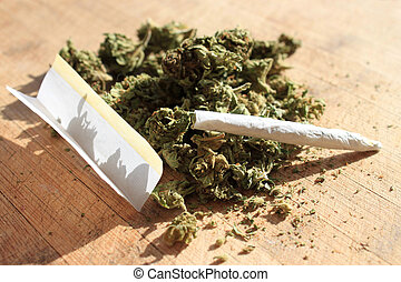Marijuana - Green cannibis with rolling paper and joint on a...