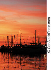 Marina at night - Boats silhouettes at sunset over the water