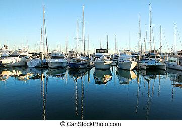 Expensive yachts and boats lined up at the marina at daybreak.