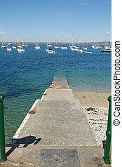 A set of concrete steps leads into the clear waters of a marina with moored yachts and a breakwater in the background.