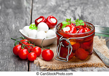 Marinated cherry tomatoes stuffed with mozzarella and spices on wooden table