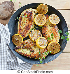 Marinated chicken breast with organic lemon in iron pan