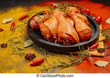 Marinated chicken drumstick on a black plate .
