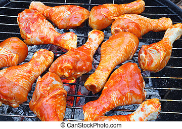 Marinated chicken legs on the grill