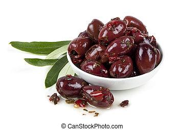 Bowl of marinated kalamata olives with olive leaves, isolated on white.