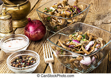 Marinated mushrooms and onions in a glass salad bowl