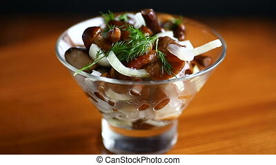 Marinated mushrooms with onions on a wooden table