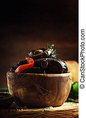 Marinated mushrooms with pepper and garlic in a wooden bowl, selective focus