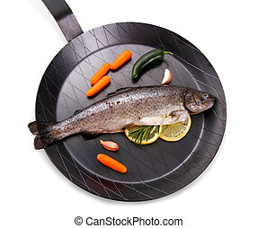 Marinated Rainbow trout with lemon on frying pan, top view