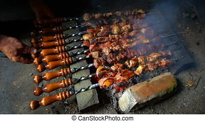 Marinated shashlik preparing on a barbecue grill over...