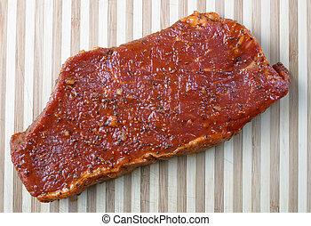 marinated steak - A marinated beef steak on a cutting board....