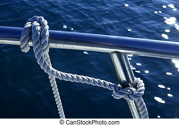 Nautical marine fender knot around stainless steel lee on blue ocean sea