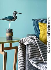 Marine style in the interior of the apartment - a sofa with pillows and the figure of a sea gull
