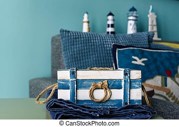 Marine style in the interior of the apartment - a sofa with pillows and the striped casket. Blue room marine concept.