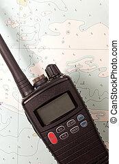Marine VHF Radio - A marine vhf radio lying on an old chart