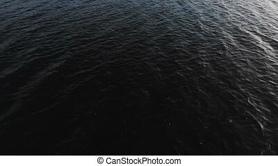 Marine video background. The air view on the dark surface of...