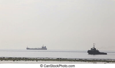 maritime port - two barges floating over the sea in time...