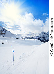 Marked slope for skiing in mountains with peaks and clouds...