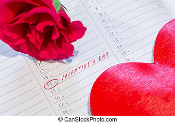 Marked the Valentine's day on calendar with rose and heart.