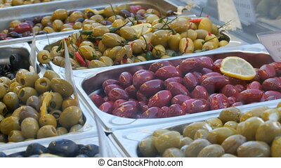 Market counter with various stuffed olives of green, red, black. Vegetarian food